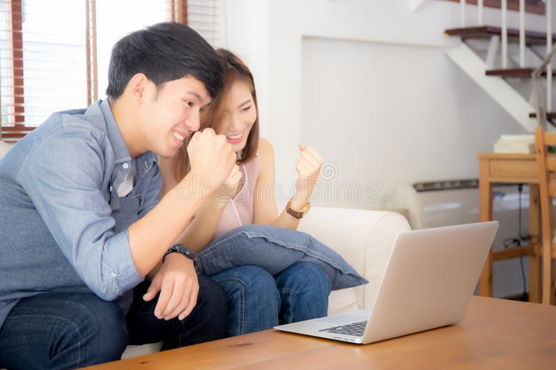 Beautiful portrait asian young couple working laptop with smile and happy sitting on couch at living room. Men and women on sofa using notebook computer with stock photo