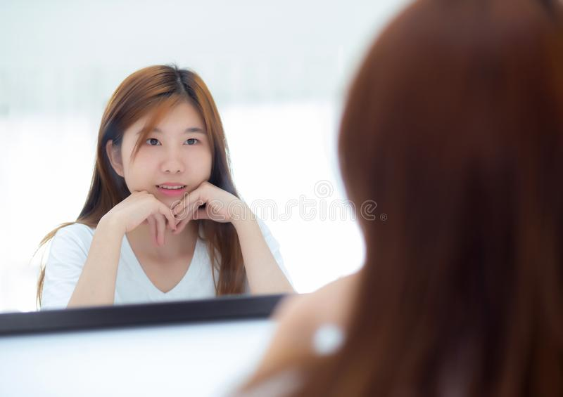 Beautiful of portrait asian young woman examining with face and smile looking on mirror at bedroom, girl beauty of makeup and royalty free stock photography