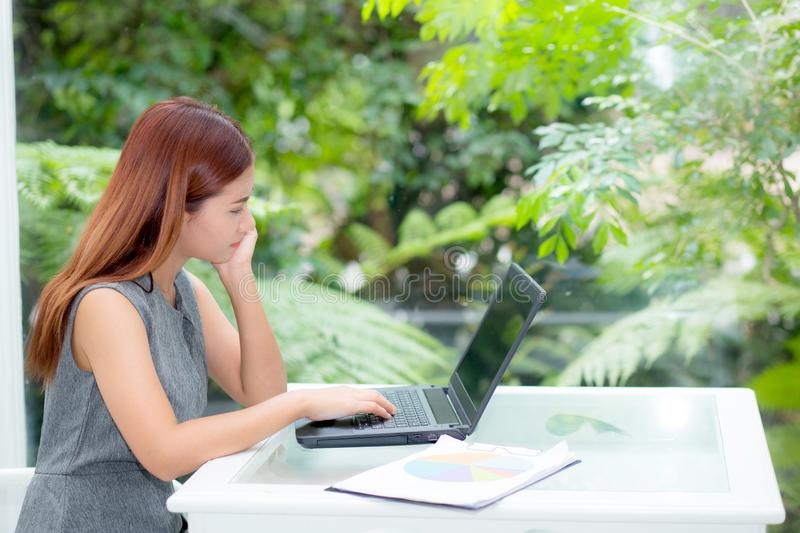 Beautiful of portrait asian young woman working online on laptop computer with graph paper sitting at office royalty free stock image