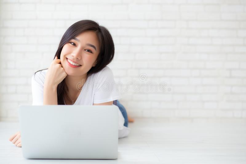 Beautiful of portrait asian young woman working online laptop lying on floor brick cement background stock photos