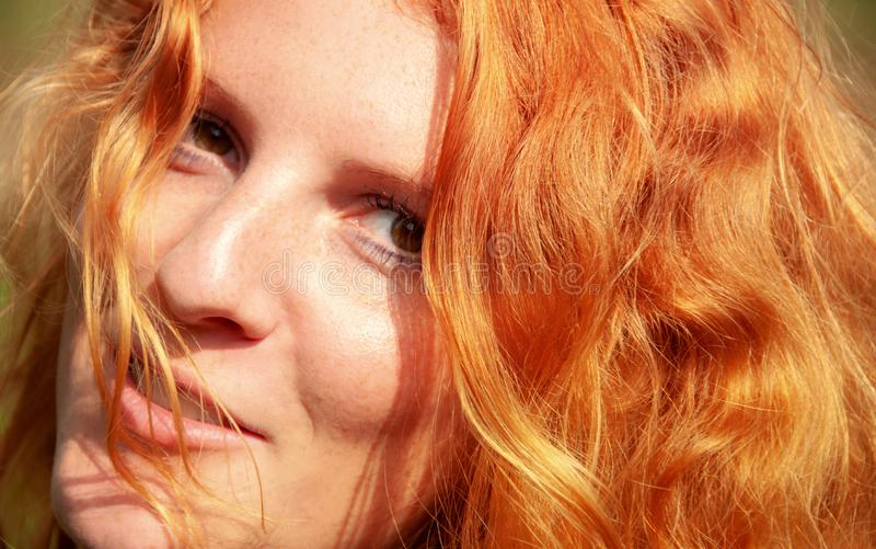 Beautiful portrait in closeup of a smiling young red-haired curly woman stock photo