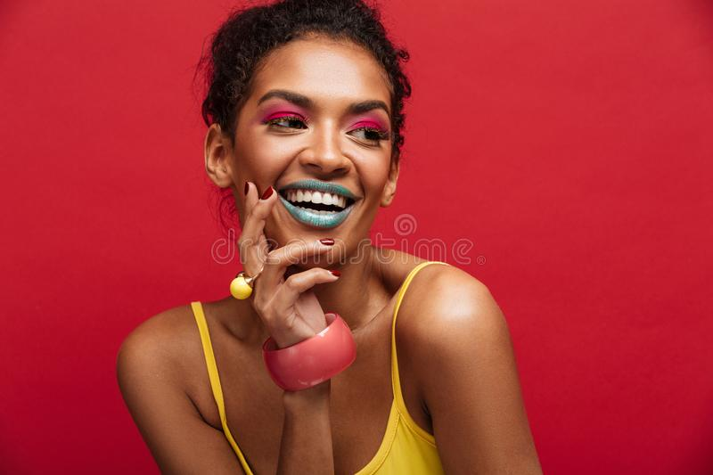 Beautiful portrait of happy african american female model in yellow shirt smiling and posing on camera, isolated over red stock photography