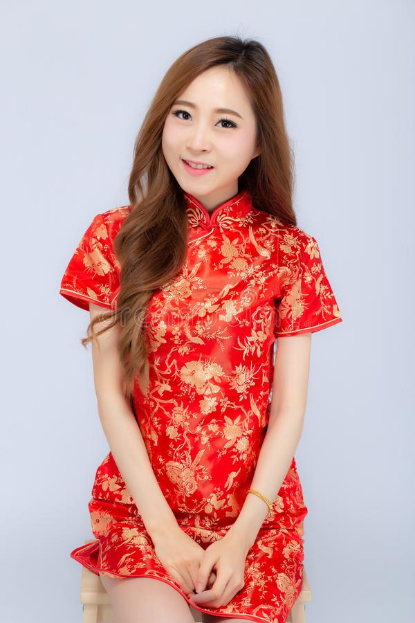 Beautiful portrait happy Chinese New Year young asian woman wear cheongsam smile with gesture congratulation and greeting isolated. On white background royalty free stock photography