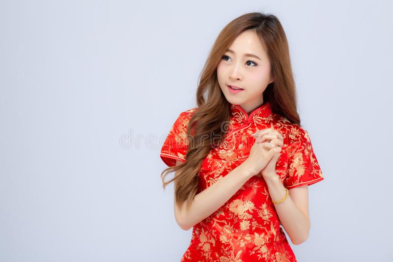 Beautiful portrait happy Chinese New Year young asian woman wear cheongsam smile with gesture congratulation and greeting isolated. On white background stock images
