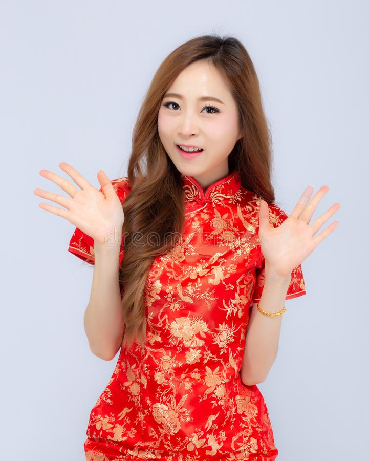 Beautiful portrait happy Chinese New Year young asian woman wear cheongsam smile with gesture congratulation and greeting isolated. On white background royalty free stock photo
