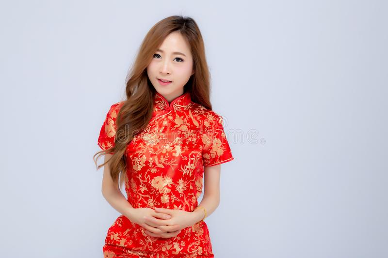 Beautiful portrait happy Chinese New Year young asian woman wear cheongsam smile with gesture congratulation and greeting isolated. On white background royalty free stock images