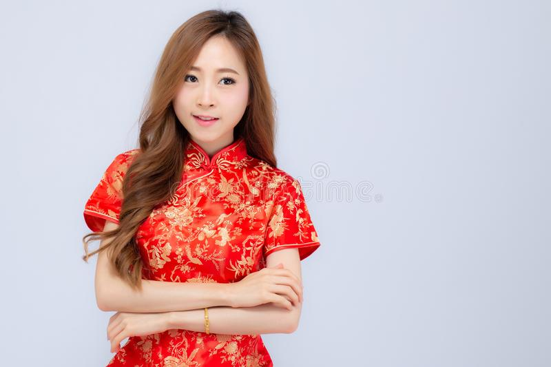 Beautiful portrait happy Chinese New Year young asian woman wear cheongsam smile with gesture congratulation and greeting. On white background, festival and royalty free stock photos