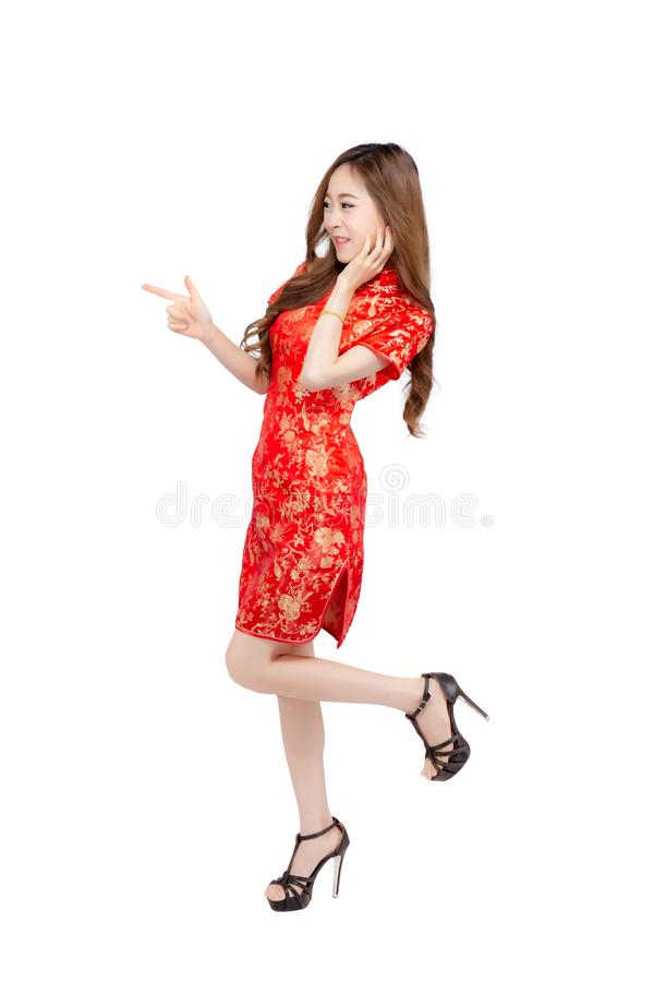 Beautiful portrait happy Chinese New Year young asian woman wear cheongsam smile presenting something with gesture finger pointing. Isolated on white background stock photo