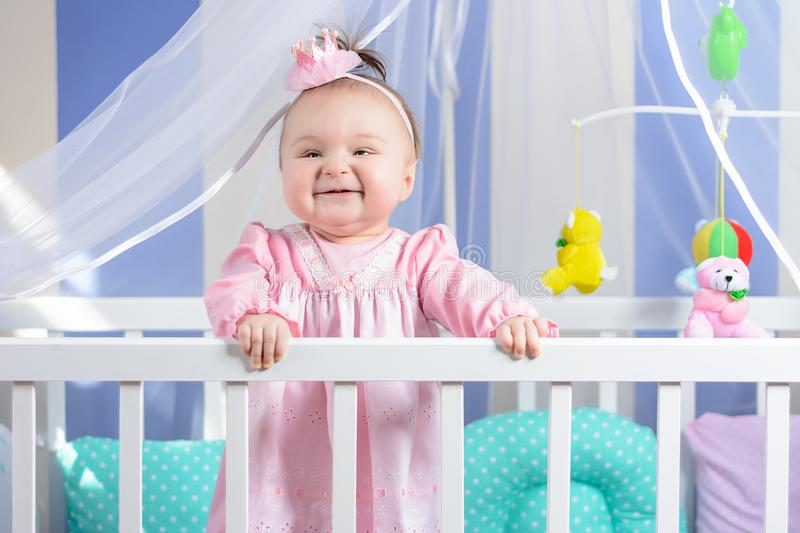 Beautiful portrait of a little girl in a pink dress in a nursery royalty free stock images