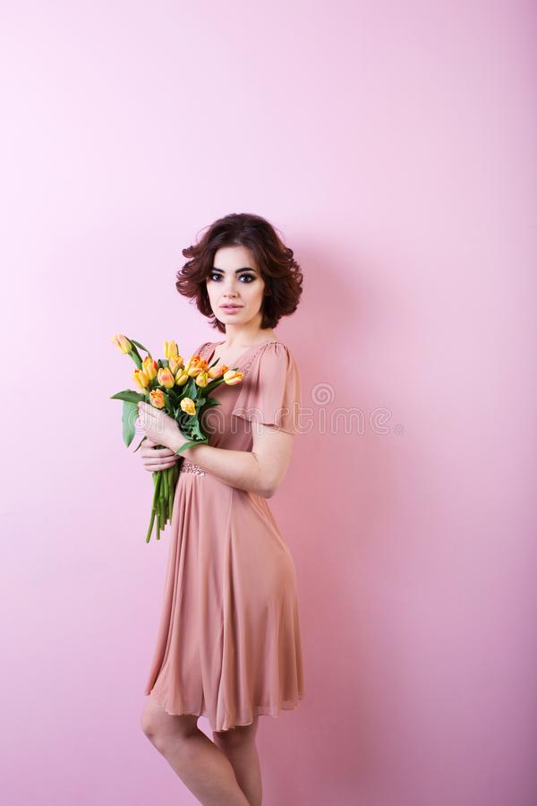 Beautiful portrait of pretty woman with bouquet of flowers over pink. stock photography