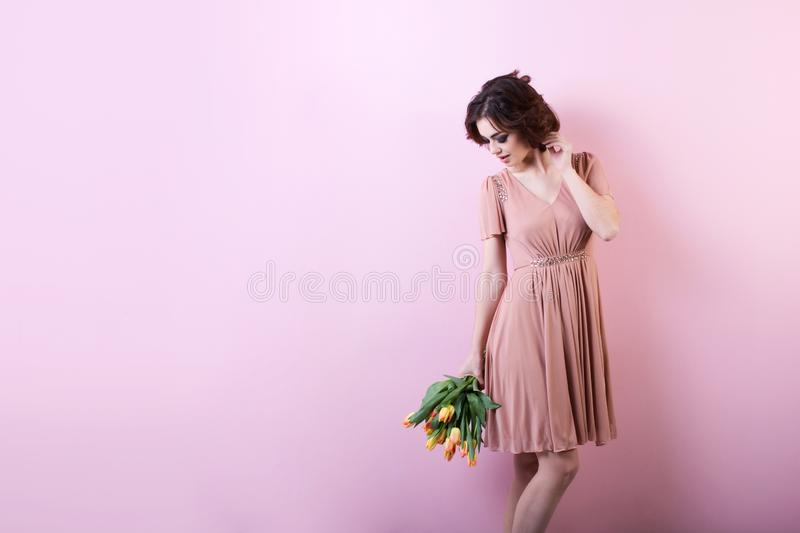 Beautiful portrait of pretty woman with bouquet of tulips over pink. royalty free stock photos