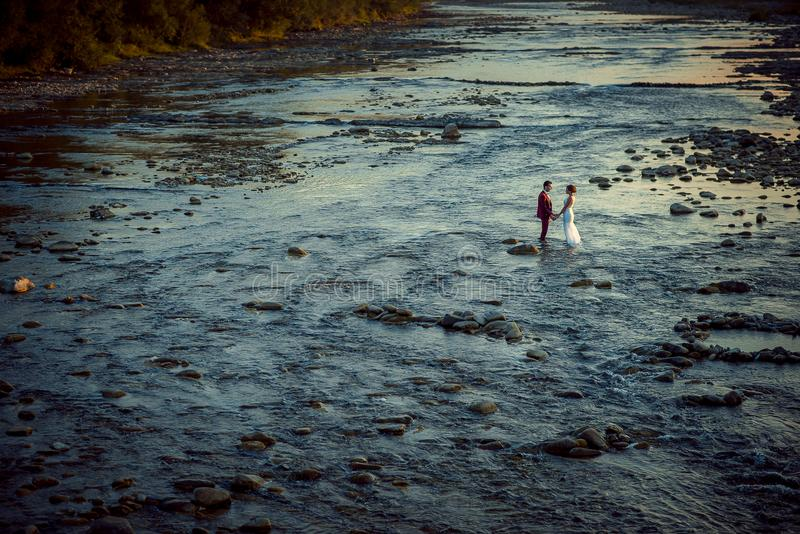 Beautiful portrait of the stylish newlywed couple holding hands in the middle of the river during the sunset. royalty free stock photos