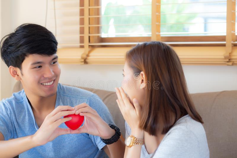 Beautiful portrait young asian couple gesture holding heart shape together, husband give heart shape wife cheerful smiling. And happy sitting on couch, family stock photography
