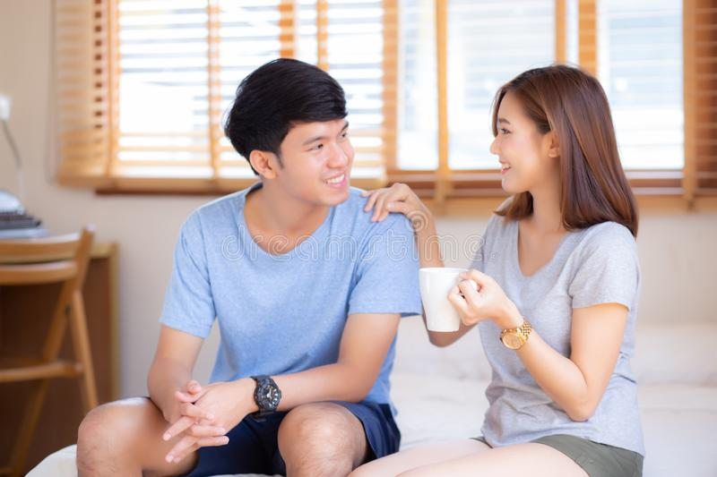 Beautiful portrait young asian couple give a cup of coffee with smiling and happy together. Family take care with health, men give water women in the bedroom royalty free stock image