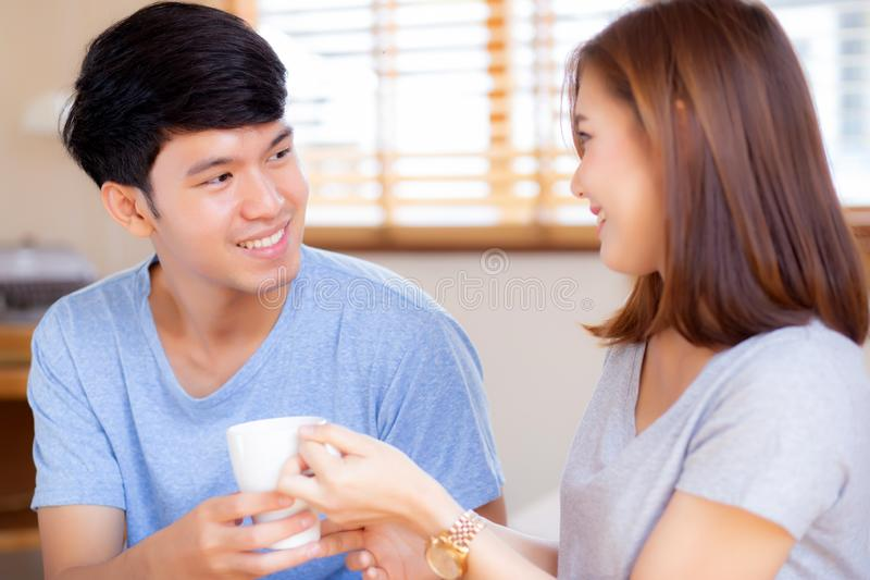 Beautiful portrait young asian couple give a cup of coffee with smiling and happy together. Family take care with health, men give water women in the bedroom stock photography