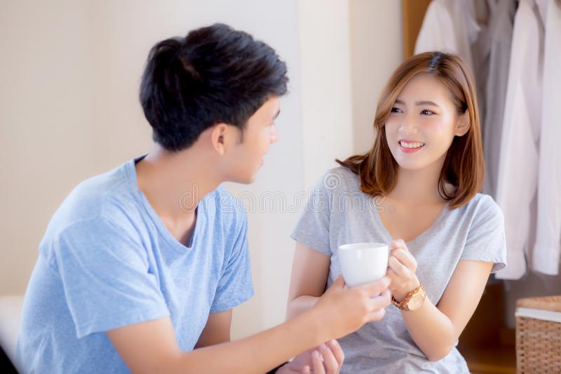 Beautiful portrait young asian couple give a cup of coffee with smiling and happy together. Family take care with health, men give water women in the bedroom stock photo