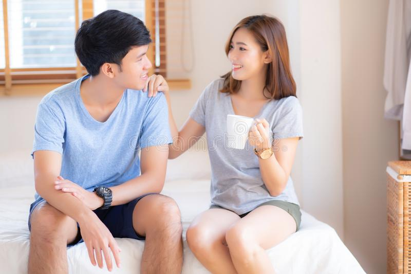 Beautiful portrait young asian couple give a cup of coffee with smiling and happy together. Family take care with health, men give water women in the bedroom royalty free stock photography