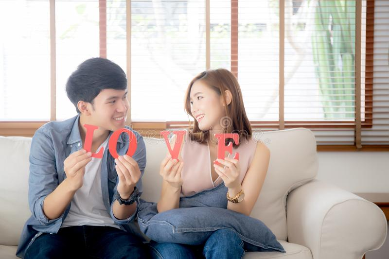 Beautiful portrait young asian couple sitting on sofa holding word love together in living room royalty free stock photos