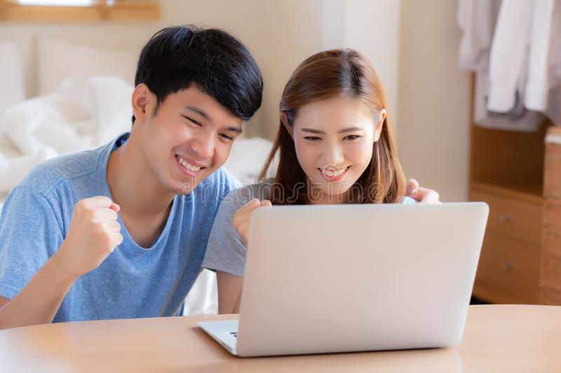 Beautiful portrait young asian couple working laptop with smile and happy sitting in bedroom. Men and women using notebook computer with excited and satisfied royalty free stock photo