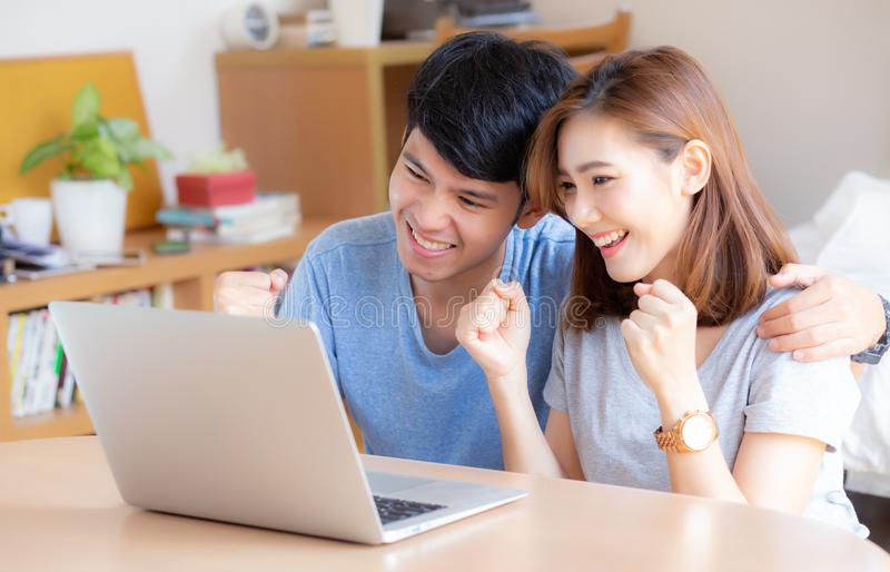 Beautiful portrait young asian couple working laptop with smile and happy sitting in bedroom. Men and women using notebook computer with excited and satisfied royalty free stock photography