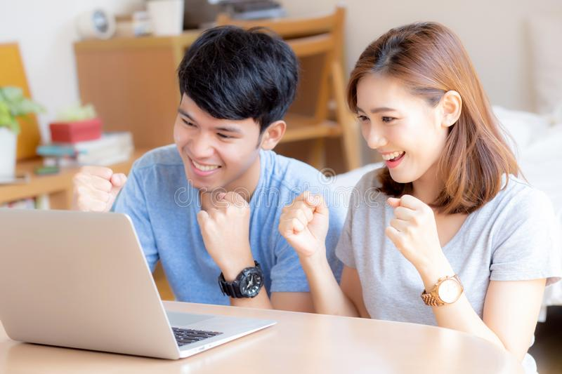 Beautiful portrait young asian couple working laptop with smile and happy sitting in bedroom. Men and women using notebook computer with excited and satisfied royalty free stock images