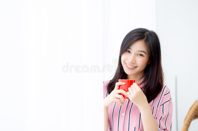 Beautiful of portrait young asian woman with drink a cup of coffee standing curtain window background in bedroom, girl relax in m. Orning at home, lifestyle royalty free stock photos