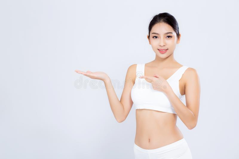 Beautiful portrait young asian woman fit smiling gesture showing presenting something empty on hand isolated royalty free stock images