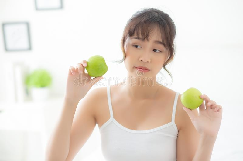 Beautiful portrait young asian woman holding and eating green apple fruit in the bedroom at home. Lifestyle of nutrition girl healthy and care weight loss royalty free stock photography