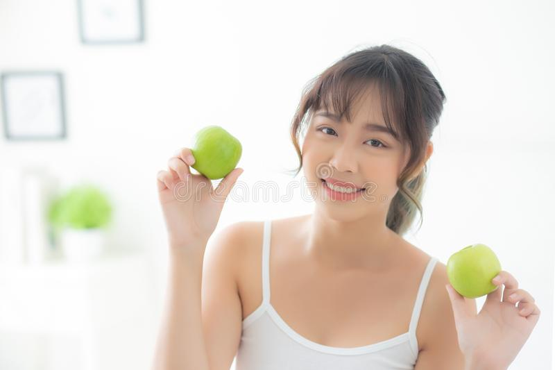 Beautiful portrait young asian woman holding and eating green apple fruit in the bedroom at home. Lifestyle of nutrition girl healthy and care weight loss royalty free stock photo