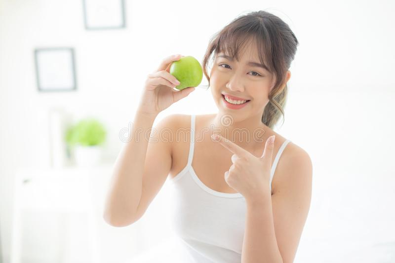 Beautiful portrait young asian woman holding and pointing green apple fruit in the bedroom at home. Lifestyle of nutrition girl healthy and care weight loss stock photos