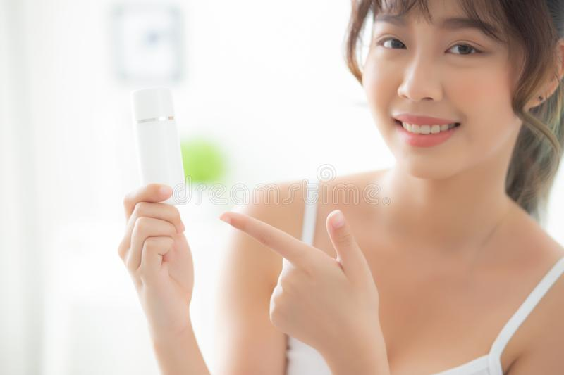 Beautiful portrait young asian woman holding and pointing presenting cream or lotion product royalty free stock image