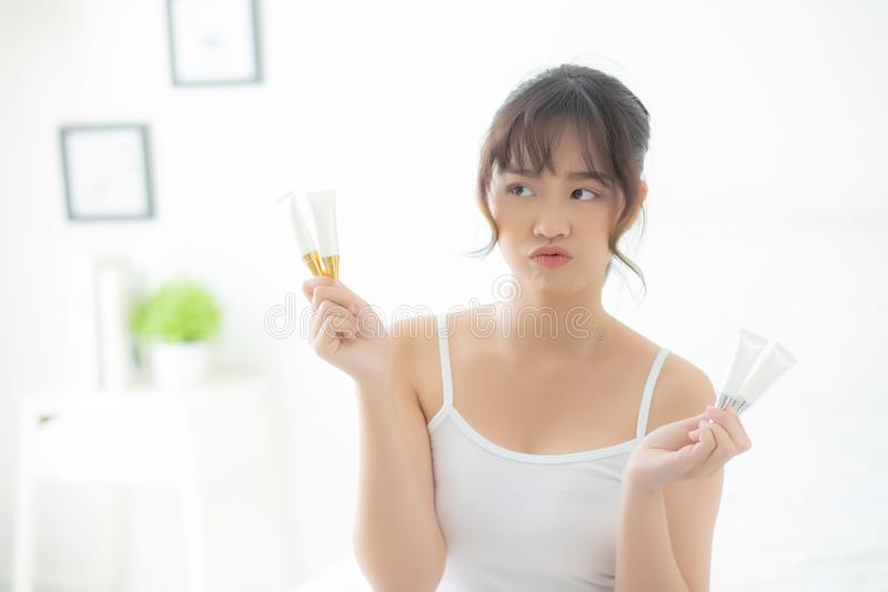 Beautiful portrait young asian woman holding and presenting cream or lotion product. Beauty asia girl show cosmetic makeup and moisturizing for skin care stock photos