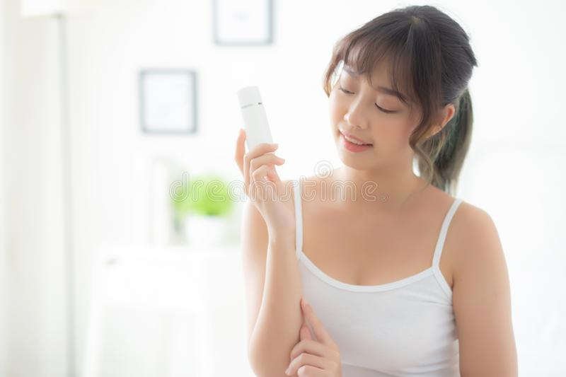 Beautiful portrait young asian woman holding and presenting cream or lotion product. Beauty asia girl show cosmetic makeup and moisturizing for skin care royalty free stock image