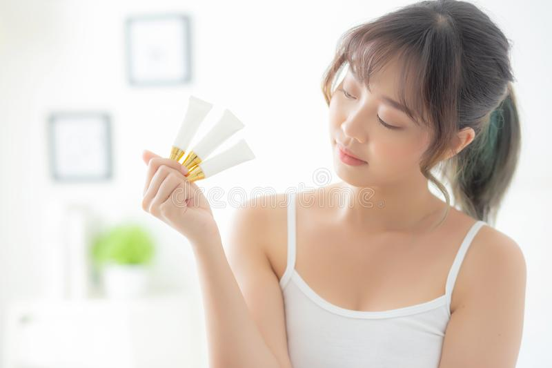 Beautiful portrait young asian woman holding and presenting cream or lotion product. Beauty asia girl show cosmetic makeup and moisturizing for skin care royalty free stock images