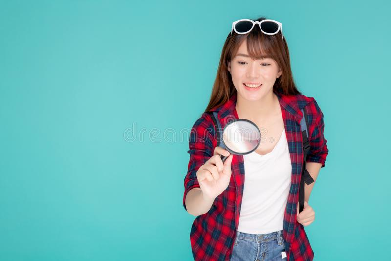 Beautiful portrait young asian woman looking something with magnify glass for planning guide to travel summer trip. Asia girl search route and location for stock image