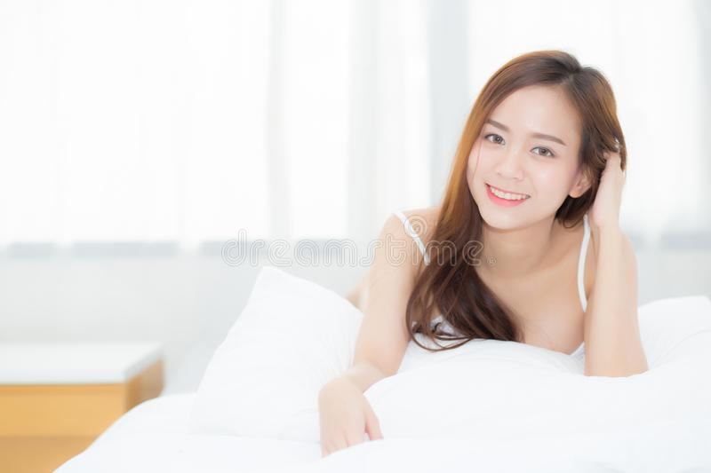 Beautiful portrait young asian woman lying and smile while wake up with sunrise at morning. royalty free stock image