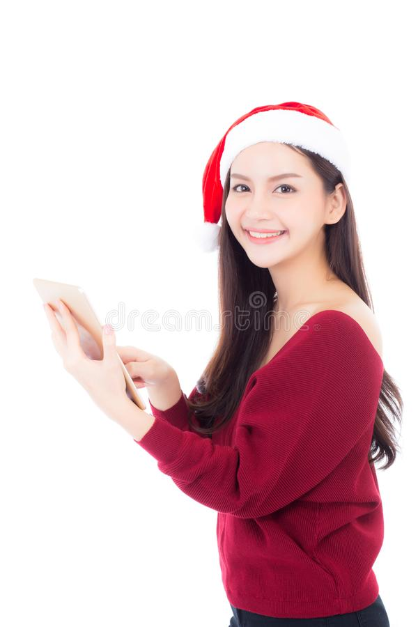 Beautiful of portrait young asian woman in red dress with christmas hat holding tablet isolated. On white background, girl with connection digital stock photo