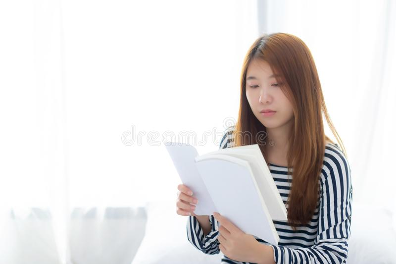 Beautiful of portrait young asian woman relax sitting reading book on bedroom at home, girl study literature, education and stock image