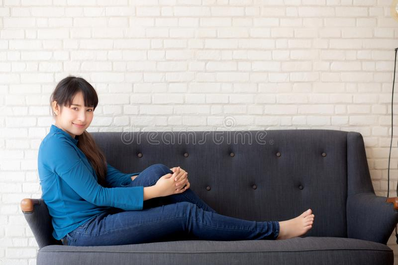 Beautiful portrait young asian woman sitting and smiling happy and looking at camera on sofa with casual at living room royalty free stock photos