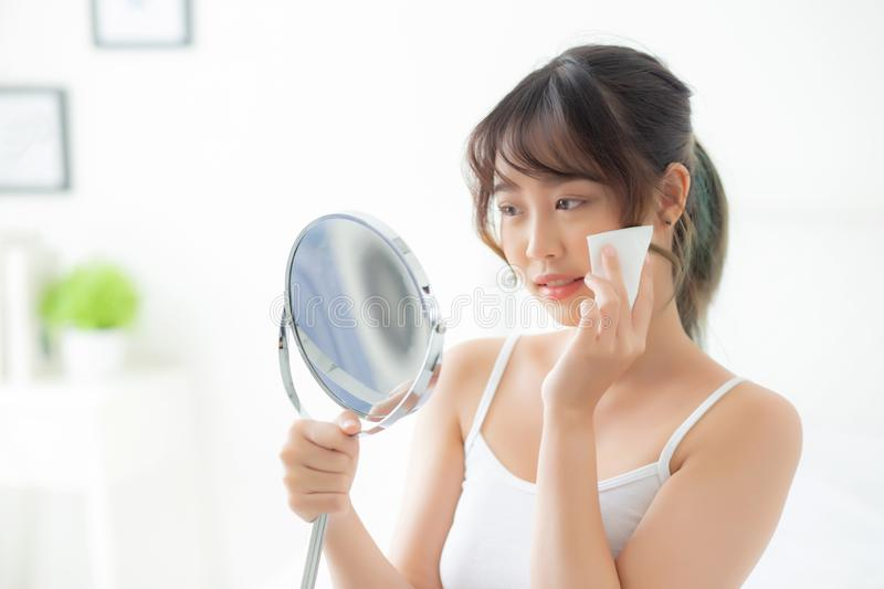 Beautiful portrait young asian woman smile and joy with skin care use oil blotting paper on face looking mirror in the room stock images