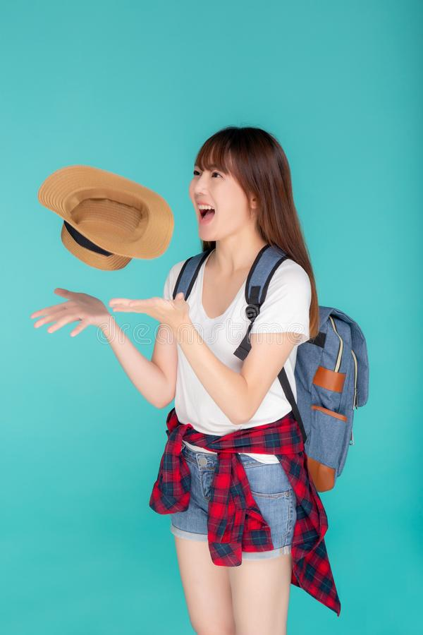 Beautiful portrait young asian woman smiling and throw hat and camera travel summer trip in vacation. On blue background, tourist asia girl cheerful journey stock photo
