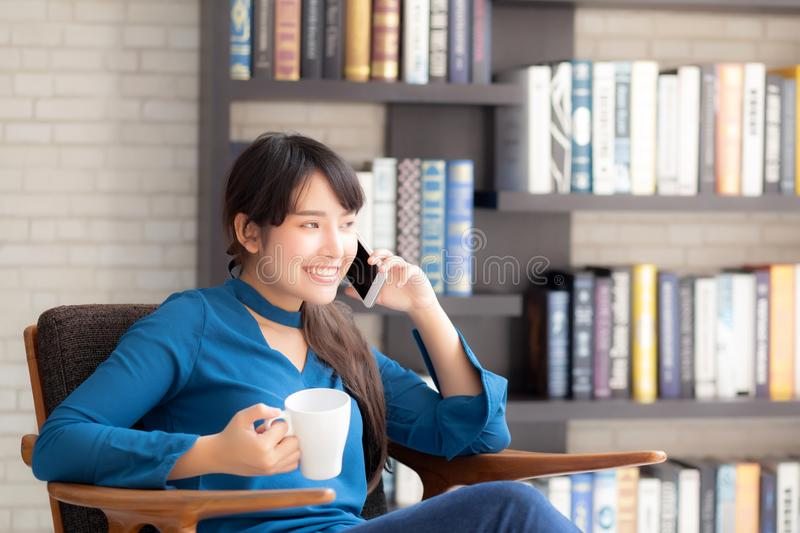 Beautiful portrait young asian woman smiling using mobile smart phone talking enjoy and drink coffee with relax royalty free stock photography