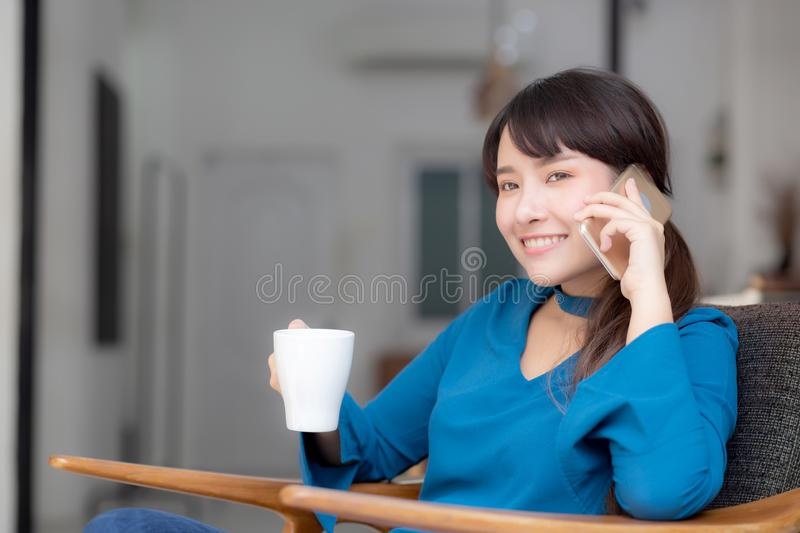 Beautiful portrait young asian woman smiling using mobile smart phone talking enjoy and drink coffee with relax stock photos