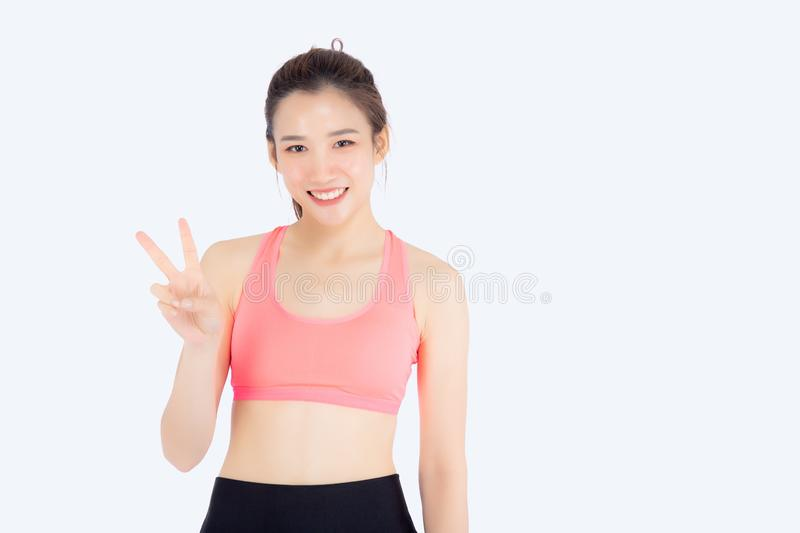 Beautiful portrait young asian woman in sport clothes with satisfied and confident gesture finger v sign isolated. On white background, asia girl have shape and stock images