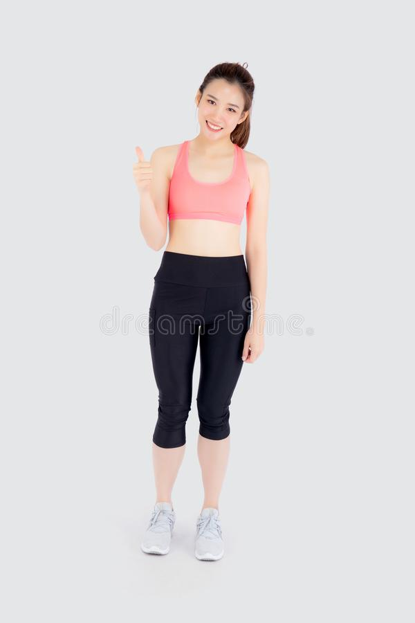 Beautiful portrait young asian woman in sport clothes with satisfied and confident gesture thumbs up isolated. On white background, asia girl have shape and stock photo