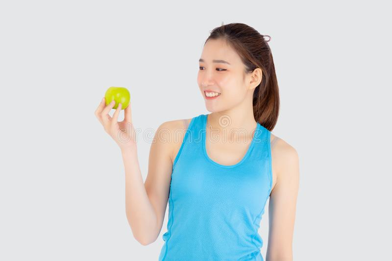 Beautiful portrait young asian woman in sport clothing with satisfied and holding green apple isolated. On white background, girl asia have shape and wellness stock photo