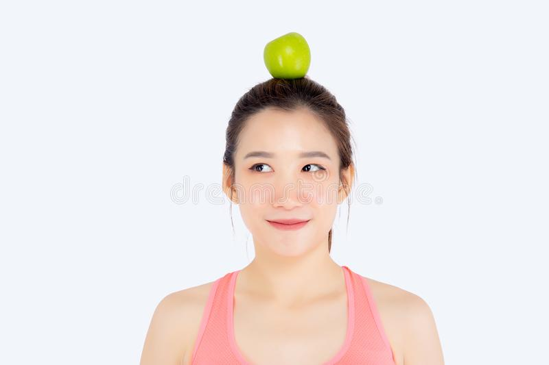 Beautiful portrait young asian woman in sport with satisfied and green apple on head isolated on white background. Girl asia have shape and wellness, exercise stock photography