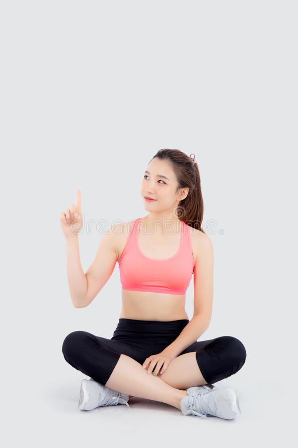 Beautiful portrait young asian woman in sport workout confident pointing and presenting and show something isolated. On white background, asia girl exercise for stock photography