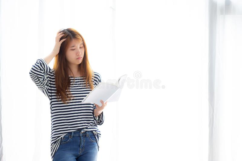 Beautiful portrait young asian woman standing reading book for exam with serious and stress in the room at home. Asia girl is student learning study with stock images