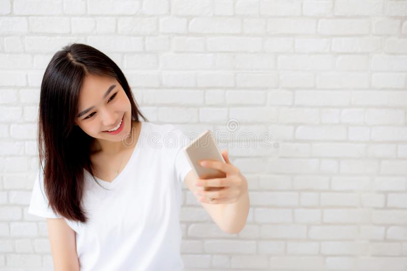 Beautiful portrait young asian woman taking a selfie with smart mobile phone on concrete cement white background royalty free stock photos